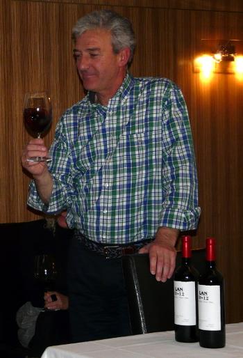 Eduardo Evangelio de pies mirando una copa de vino tinto. BodegasLAN. Restaurante Sotavento Santurtzi